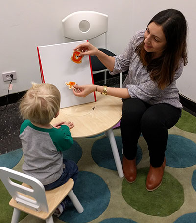 Amanda Lossia, a graduate student researcher, engages a child in a task designed to gather information to build the game.